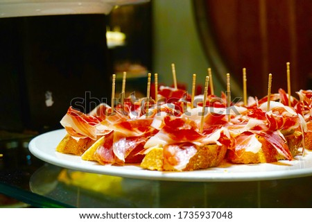 Tapas food canapés spanish restaurant ham parma prosciutto eat dine platter party feast finger food red meat sliced meat jamon iberico cured ham mountain ham cafe standup takeout dinner snack bread  Photo stock ©