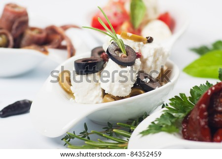 Tapas with cheese, olives and rosemary, selective focus