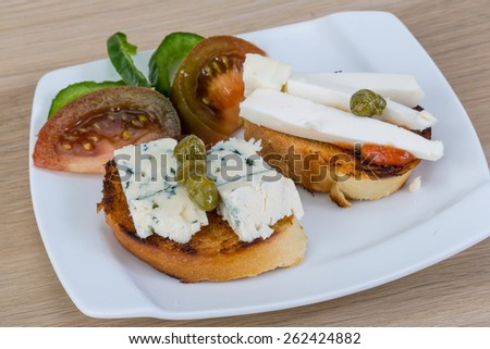 Tapas with soft blue cheese and black tomato