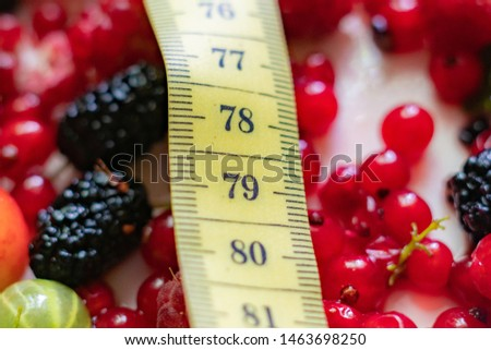 tape centimeter scale  on top of fresh berries, diet concept, flat lay