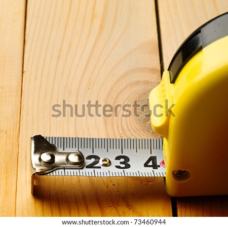 Tape measure isolated on wooden background
