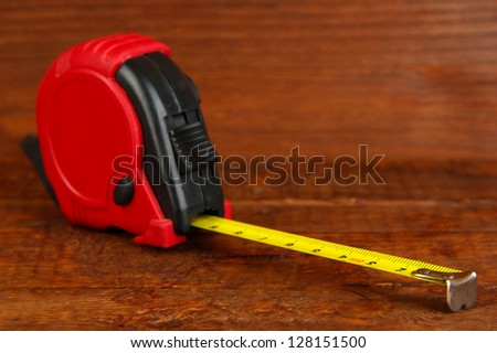 Tape measure on wooden background