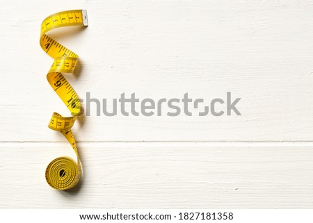 Tape measure sewing tool over white wooden table background with copy space, top view flat lay from above Foto stock ©