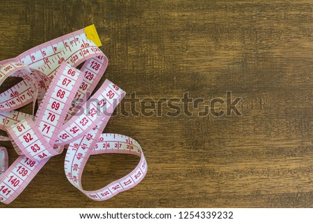 tape measure with wooden background and empty space for text.