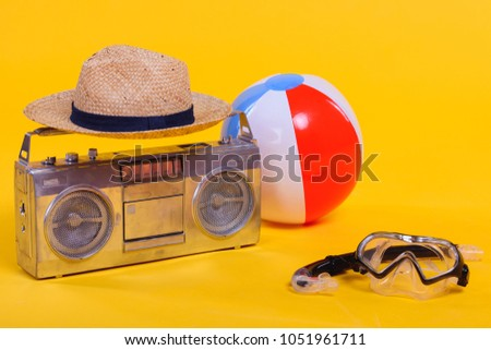 tape recorder, hat, beach ball and snorkel with scuba mask isolated on yellow #1051961711