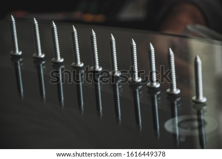 Tapping screws made of steel in a straight line. Metal screw, iron screw, chrome screw. Dark background.
