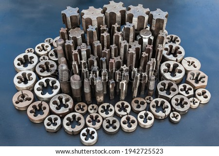 Taps and dies for metal threading. Tools for cutting external and internal threads, close-up.Taps and dies for metal threading. Tools for cutting external and internal threads, close-up.