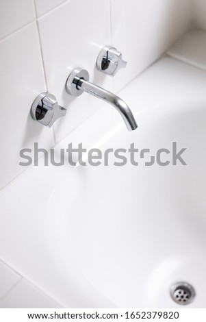 Taps and spout on white bath with plug hold simple clean modern