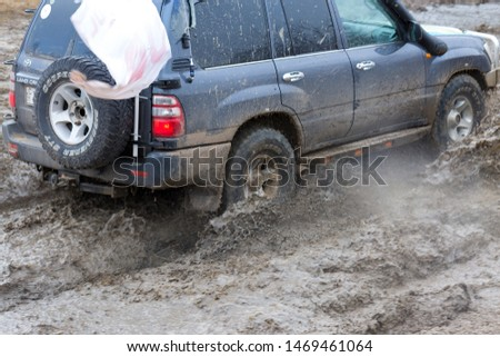 Taraclia, Moldova - 23. 02. 2019: Rally on Nissan SUVs in the mud in winter, All-terrain vehicle crosses the river    #1469461064