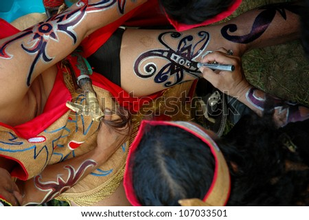 TARAKAN, INDONESIA - DEC 18: Unidentified dancers create tattoos on their bodies at the event Iraw Tengkayu festival on Dec 18, 2011 at Amal Beach Tarakan, Indonesia