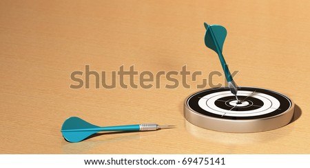 Target and two darts on a wooden table, the first dart hit the center of the target the 2 darts are blue