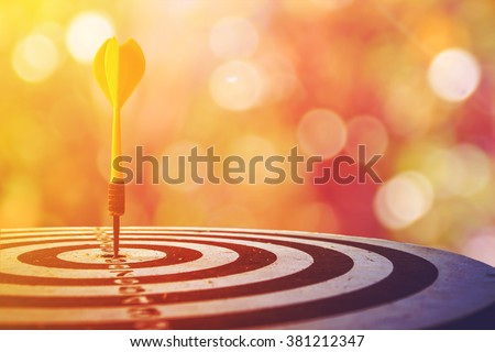 target dart with arrow over blurred bokeh background ,metaphor to target marketing concept.
