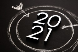 target drawn in white chalk on a black background with the numbers 2021. Goals and plans for the new year. eve 2021
