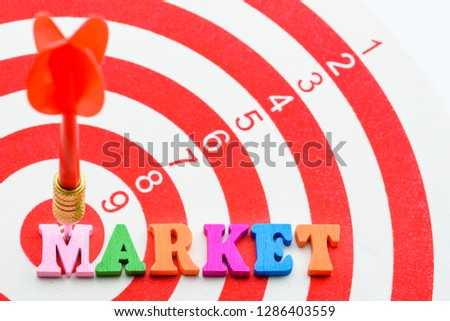 Target market concept : Red dart hits in the center of a target or bullseye or dart board, depicts the market a company wants to sell products and service, includes a targeted set of customers / buyer