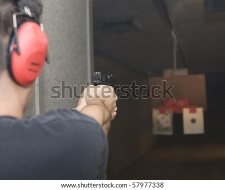 Target practicing with gun In the shooting range