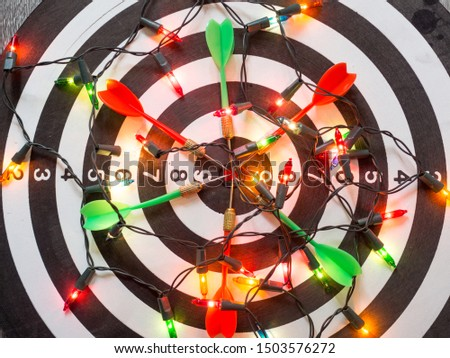 Target six dart focus on bull's eye Dart Board with party light, Funly setting challenging business goals And ready to achieve the goal concept. #1503576272