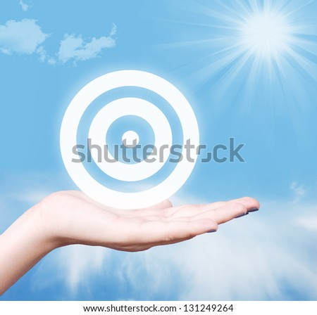 Target symbol in human hand against blue sky. Strategy concept.