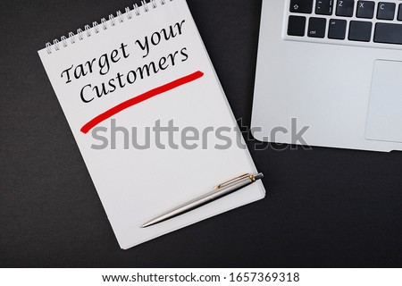 Target your customers hope in a notebook lying on a dark background with a pen and laptop