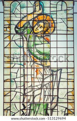 Targoviste, Romania - November 05, 2016: Bright and colorful stained glass window representing a saint. Church mosaic window #513129694