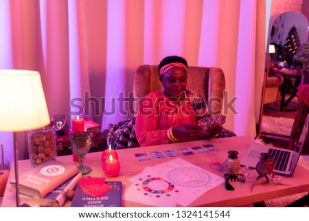 Tarot. African american plump fortune-teller wearing ethnic adornments reading cards Tarot
