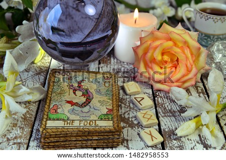Tarot cards deck, crystal ball, runes and flowers on witch table. Esoteric, gothic and occult concept, Halloween mystic background, divination ritual