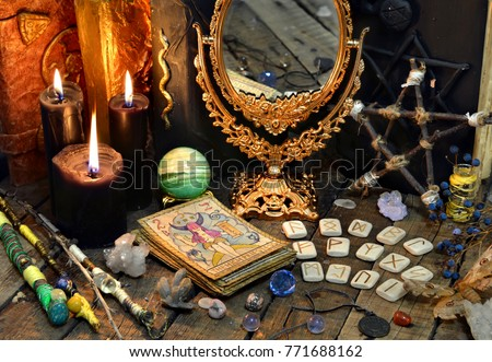 Tarot cards, magic wands, runes, black candles with mirror and old book. Occult, esoteric, divination and wicca concept. Mystic and vintage background  #771688162