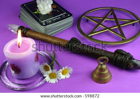 Tarot cards, pentacle, crystal, candle, wand, bell and flowers - stock photo