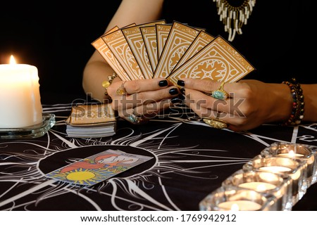 Tarot reader or fortune teller of hands holding up deck tarot cards.Tarot cards spread and The Sun card on table near burning candles.The Sun card portends good fortune, happiness ,joy and harmony. Photo stock ©