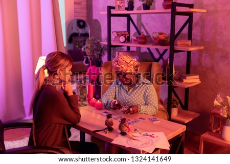 Tarot reading. African american plump fortune-teller wearing a huge ring reading Tarot