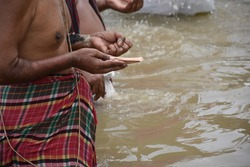 Tarpan is being performed by Indian hindu devotees on the banks of the holy river Ganga in Kolkata, India. In Hindu mythology this day is also called Mahalaya.