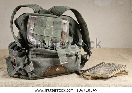 Tarpaulin backpack and old books on the canvas