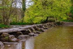 Tarr Steps Bridge in Devon tourist destination South West England UK crossing over water old historic stones tree hanging safe