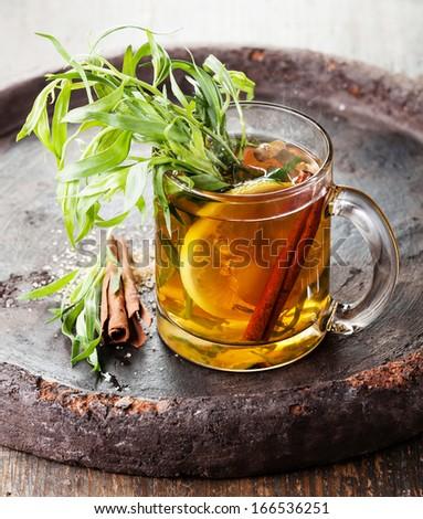 Tarragon hot drink tea with honey, lemon and cinnamon on dark ...