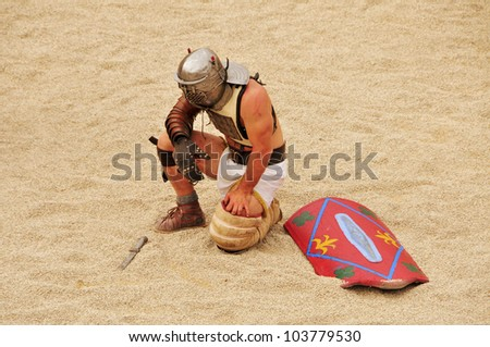 TARRAGONA, SPAIN - MAY 26: A gladiator on the arena of Roman Amphitheater on May 26, 2012 in Tarragona, Spain. Every year, the historic recreation program TarracoViva recreates a gladiators fight