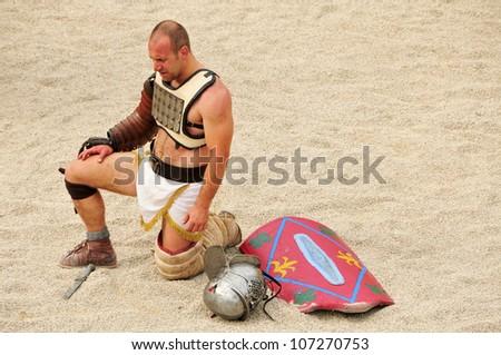 TARRAGONA, SPAIN - MAY 26: Gladiator on the arena of Roman Amphitheater on May 26, 2012 in Tarragona, Spain. Every year, the historic recreation program TarracoViva recreates a gladiators fight