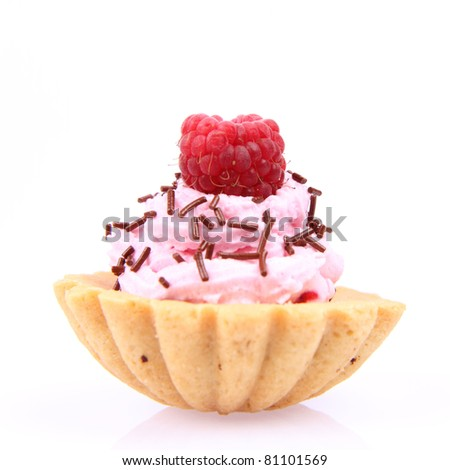 Tart-let with whipped cream, a raspberry and sprinkles on a white background