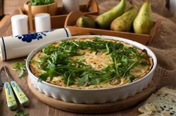 Tart with pear, blue cheese and arugula on a rustic background