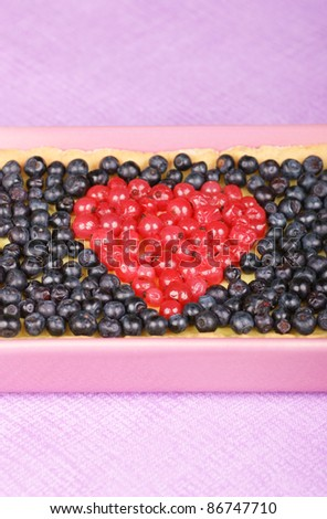 Tart with redcurrants and blueberries in a pink pottery cake tin