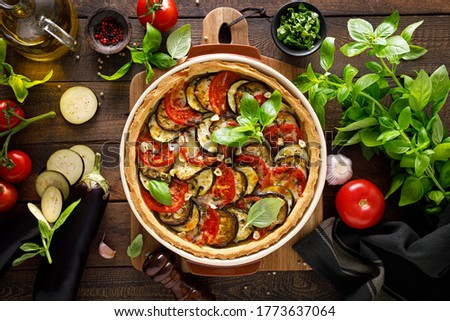 Tart with vegetables. Homemade savory tart with eggplant, zucchini, tomatoes, garlic, mozzarella cheese and fresh basil. Mediterranean  cuisine. View from above