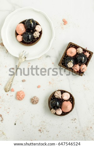 Tartlet desserts on the marble ground with dessert fork and meringues #647546524