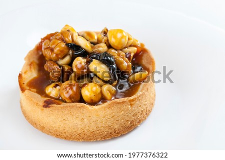 tartlet stuffed with hazelnuts, peanuts and walnuts and dried fruits, nut tartlet covered with a layer of liquid caramel, high-calorie dessert made from dough with natural ingredients