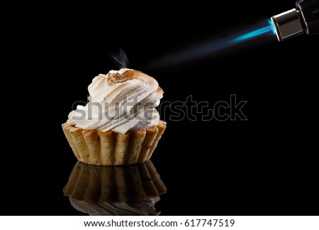 Tartlet with a meringue and kitchen torch /  blowtorch with blue flame isolated on black background. Funny sweets. #617747519