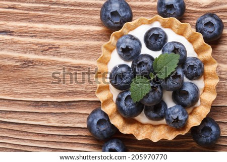 Tartlet with fresh blueberries on a wooden background horizontal view from above