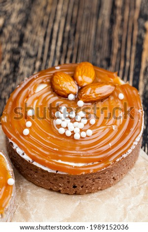tartlet with milk cheese filling and lots of salted caramel with nuts, almonds on tartlets with cottage cheese or butter cream and caramel, delicious desserts