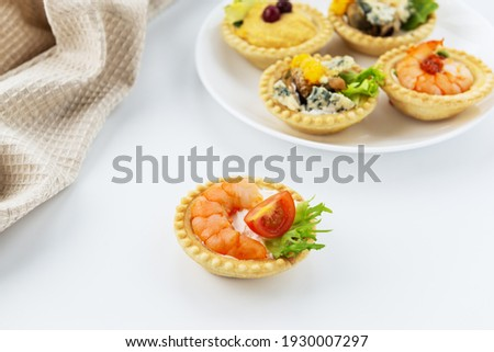 Tartlet with shrimp, tomato and cheese on the background of a set of tartlets.