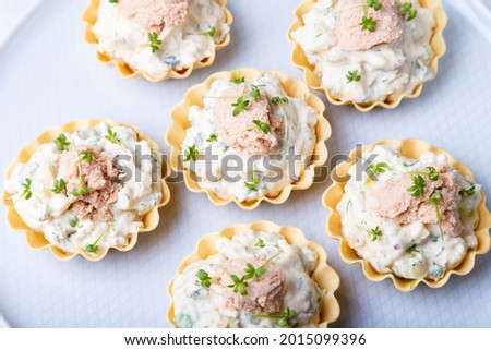 Tartlets stuffed with codfish liver, codfish caviar, cucumber and microgreens. Traditional cold portioned appetizer in a pastry basket. Close-up. Stock photo ©