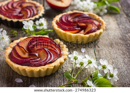 Tartlets with plum on old wooden background