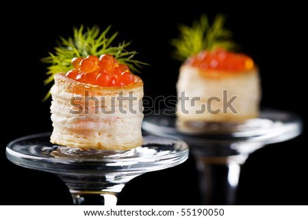 Tartlets with red caviar on black background
