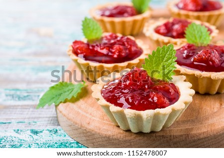 Tartlets with strawberry jam and mint on wooden background. Selective focus.