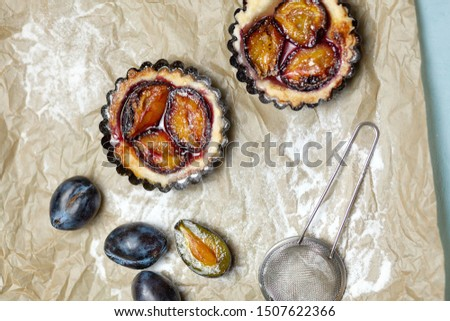 Tarts plums on the parchment. Homemade cake. Confectionery product